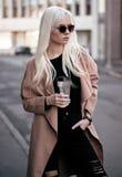 Schöne Blondine, die draußen mit Kaffee aufwerfen Stockfotos