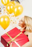 Schöne Blondine, die ein Geschenk und Ballone auf einem weißen Hintergrund halten Stockbild