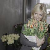 Blonde Frau, die Tulpen hält Stockfoto