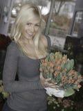 Blonde Frau, die Tulpen hält Stockbild