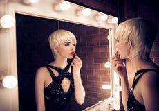 Schöne Blondine, die in einen Spiegel und Appl betrachten Stockfotos