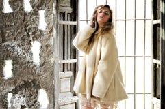Schöne Blondine, die einen weißen Mantel in einem alten Haus tragen stockfotos