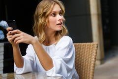 Schöne Blondine, die Handy halten und zurück schauen Lizenzfreies Stockfoto