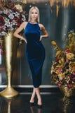 Schöne Blondine, die im blauen Kleid aufwerfen Stockfoto