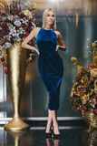 Schöne Blondine, die im blauen Kleid aufwerfen Lizenzfreie Stockfotografie