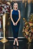 Schöne Blondine, die im blauen Kleid aufwerfen Lizenzfreies Stockfoto