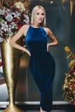 Schöne Blondine, die im blauen Kleid aufwerfen Stockbild
