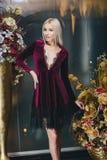 Schöne Blondine, die im Bordeauxkleid aufwerfen Stockfoto