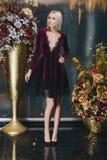 Schöne Blondine, die im Bordeauxkleid aufwerfen Stockfotografie
