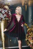 Schöne Blondine, die im Bordeauxkleid aufwerfen Lizenzfreie Stockbilder