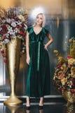Schöne Blondine, die im grünen Kleid aufwerfen Lizenzfreie Stockfotografie