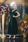 Schöne Blondine, die im grünen Kleid aufwerfen Lizenzfreie Stockbilder