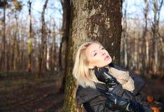 Schöne Blondine, die im Park aufwerfen Stockbilder