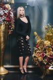 Schöne Blondine, die im schwarzen Kleid aufwerfen Lizenzfreie Stockfotos