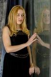 Schöne Blondine in einem Kleid sitzen in einem antiken Raum am Fenster Lizenzfreie Stockbilder