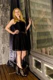 Schöne Blondine in einem Kleid sitzen in einem antiken Raum am Fenster Lizenzfreies Stockfoto