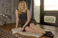 Schöne Blondine in einem Kleid sitzen in einem antiken Raum am Fenster Stockfotos