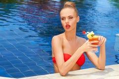 Schöne Blondine in einem Pool mit einem Cocktail Lizenzfreie Stockbilder