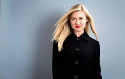 Schöne Blondine in einem schwarzen Mantel stockbilder