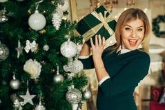 Schöne Blondine hält in seinen Händen ein Weihnachtsgeschenk und das Lächeln an der Kamera Lizenzfreie Stockfotografie