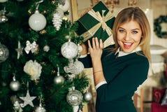Schöne Blondine hält in seinen Händen ein Weihnachtsgeschenk und das Lächeln an der Kamera Lizenzfreies Stockfoto