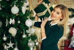 Schöne Blondine hält in seinen Händen ein Weihnachtsgeschenk und das Lächeln an der Kamera Stockfotos