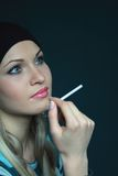 Schöne Blondine hält Zigarette Stockfoto