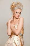Schöne Blondine im Goldkleid stockfotos