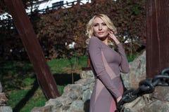 Schöne Blondine im Kleid geht in Herbst Stockfoto
