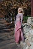 Schöne Blondine im Kleid geht in Herbst Lizenzfreies Stockfoto
