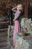 Schöne Blondine im Kleid geht in Herbst Stockbild