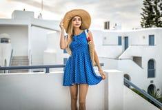 Schöne Blondine im Kleid mit Strohhutsommermode in Santorini stockfoto