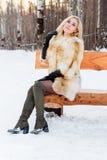 Schöne Blondine im Pelzmantel, Stiefel wirft auf Holzbank auf Stockfotos
