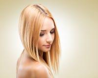 Schöne Blondine im Profil, schauend unten auf einem hellen Hintergrund Lizenzfreie Stockbilder