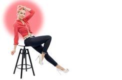 Schöne Blondine im Retrostil, der auf Schemel sitzt Lizenzfreie Stockfotografie