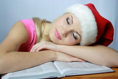 Schöne Blondine im roten Hubcap schläft auf Buch Lizenzfreie Stockbilder