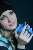 Schöne Blondine im schwarzen Hut mit Cup Lizenzfreie Stockfotos