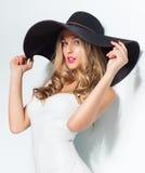 Schöne Blondine im schwarzen Hut und weißen eleganten im Abendkleid, die auf lokalisiertem Hintergrund aufwirft Art und Weiseblic Lizenzfreies Stockfoto