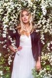 Schöne Blondine im weißen Kleid, das im Frühjahr im Blumengarten steht Stockbilder