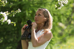Schöne Blondine mit blauen Augen Frau mit einer Kamera auf einem Hintergrund eines blühenden Gartens Stockbilder