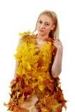 Schöne Blondine mit blauen Augen im Kleid von Blättern Stockfoto