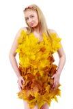 Schöne Blondine mit blauen Augen im Kleid von Blättern Stockfotos