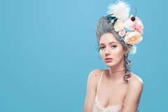 Schöne Blondine mit Blumen auf Kopf Süße sexy Dame Abbildung der roten Lilie Modefoto auf blauem Hintergrund mit Lizenzfreie Stockfotografie