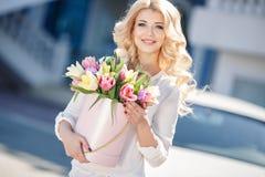 Schöne Blondine mit Blumen in der Geschenkbox lizenzfreie stockfotos
