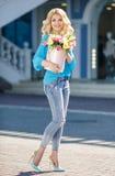 Schöne Blondine mit Blumen in der Geschenkbox Lizenzfreie Stockbilder