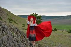 Schöne Blondine mit dem roten Mantel, der barfuß im w steht lizenzfreie stockfotografie