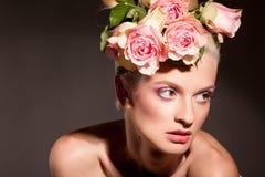 Schöne Blondine mit einem Wreath der Blumen Stockfoto