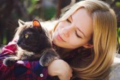 Schöne Blondine mit einer Katze in der Natur, hell und sonnig haustiere Lizenzfreies Stockfoto