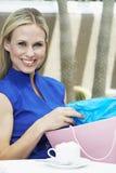 Schöne Blondine mit Einkaufstasche am Café Stockfoto