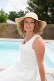 Schöne Blondine mit Hut und Weiß kleidet zum Pool an Stockfotos
